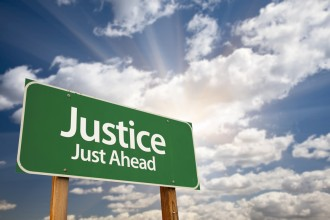 """justice just ahead"" road sign"